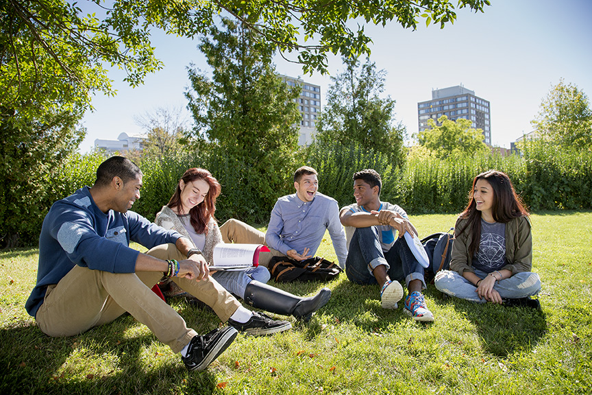 A photo of a group of friends sitting on the grass at York University.